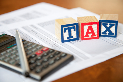 Building blocks spelling tax, with calculator and paperwork