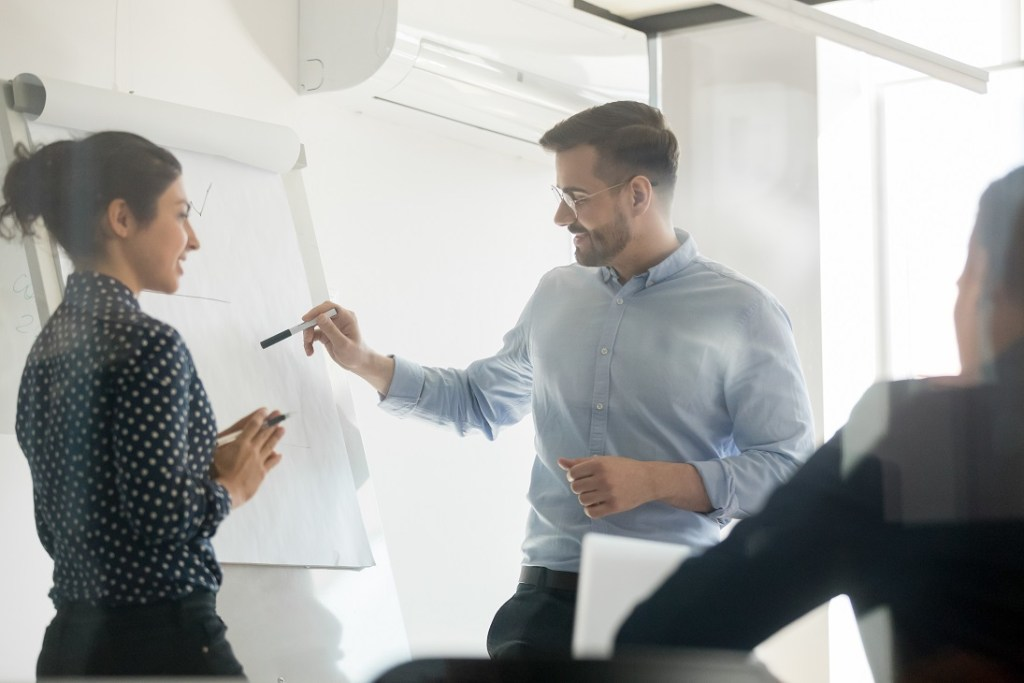 Diverse speakers make flip chart presentation in conference room