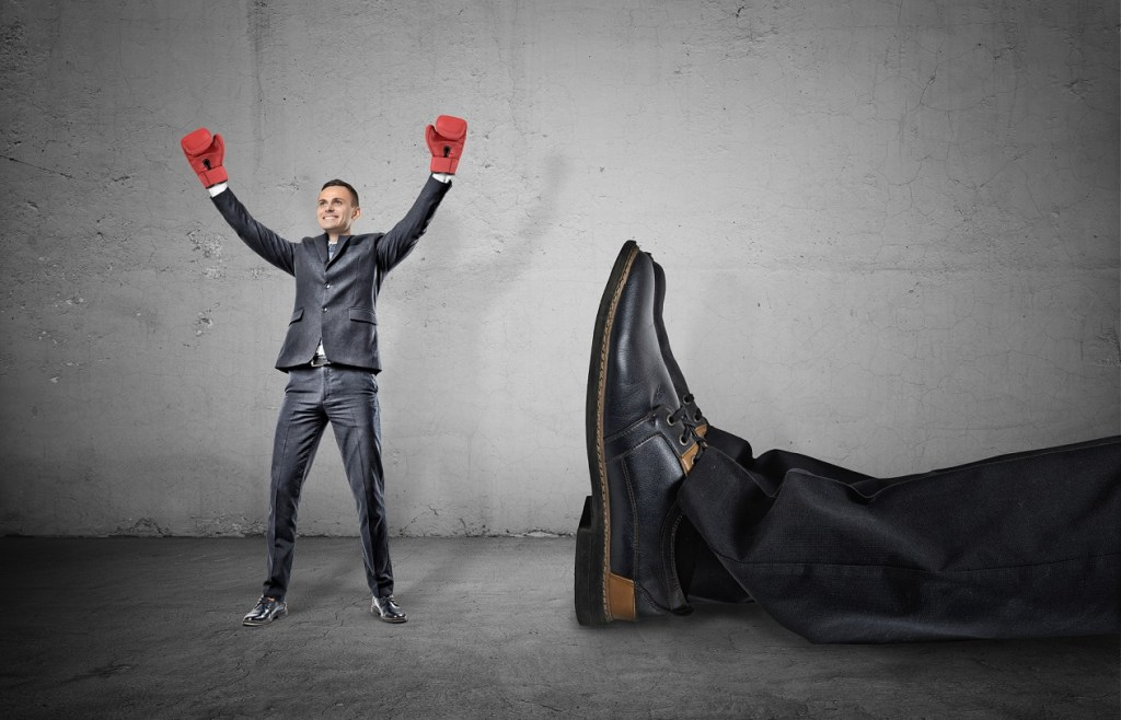 A happy businessman with boxing gloves on arms raised in victory stands near a giant male leg fallen down. Fight off competition. Unexpected winner. Chance of success.