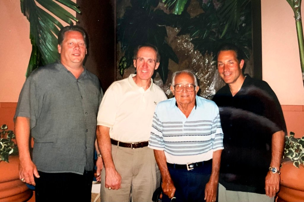 A group of men gathered together smiling