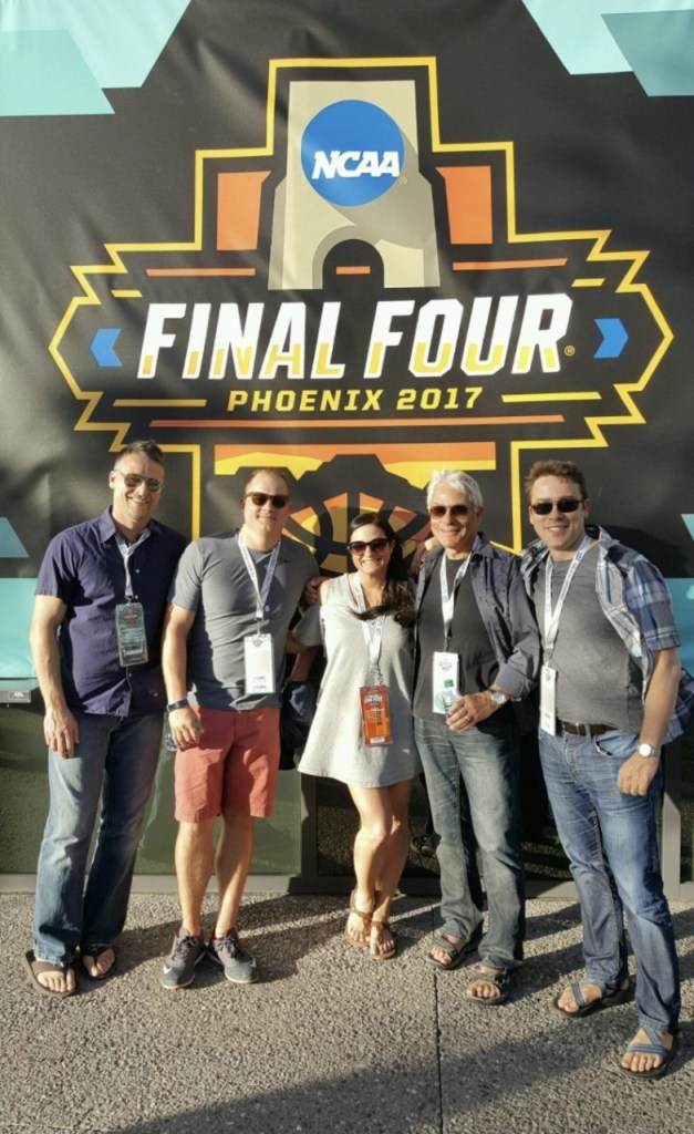 Ray and friends standing in front of NCAA banner