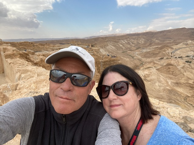 Man and woman taking a selfie at the top of a mountain