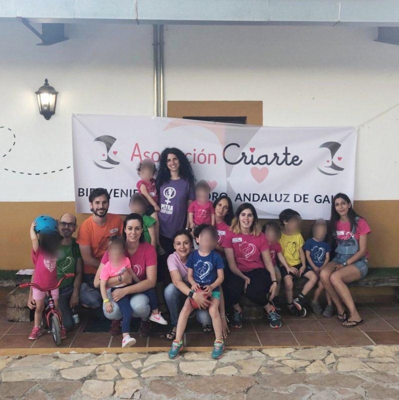 Mujeres y niños con camimseta de la asociación Mamateta delante del cartel de bienvenida al VI foro andaluz de grupos de apoyo a la lactancia