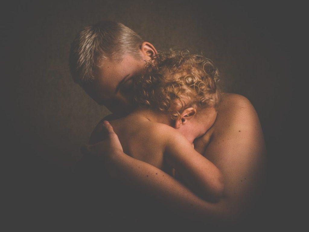 Bebé de 2 años en plena cirisis de lactancia, abrazada a su mamá