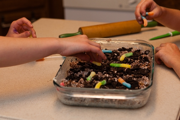 adding the worms to the dirt cake