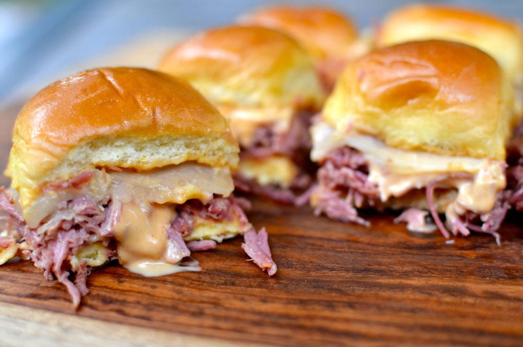 Slow cooker corned beef Reuben sliders made with tender beef, cheese and 1000 Island dressing is a family favorite dish!