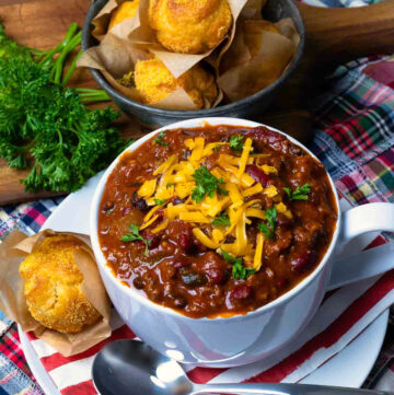 Award Winning Southern Soul Chili in a bowl topped with cheese and served with cornbread muffins.