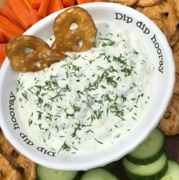 herbs and dill pickle dip with veggies and crackers.