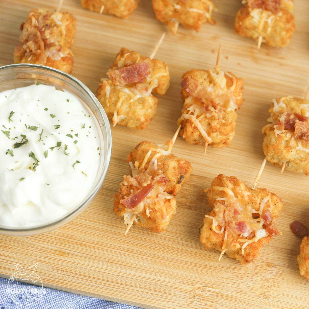 Tater Tots made into loaded little appetizer bites are a great appetizer or snack. Topped with cheese & bacon then dipped into creamy sour cream, they become a savory treat everyone will love.