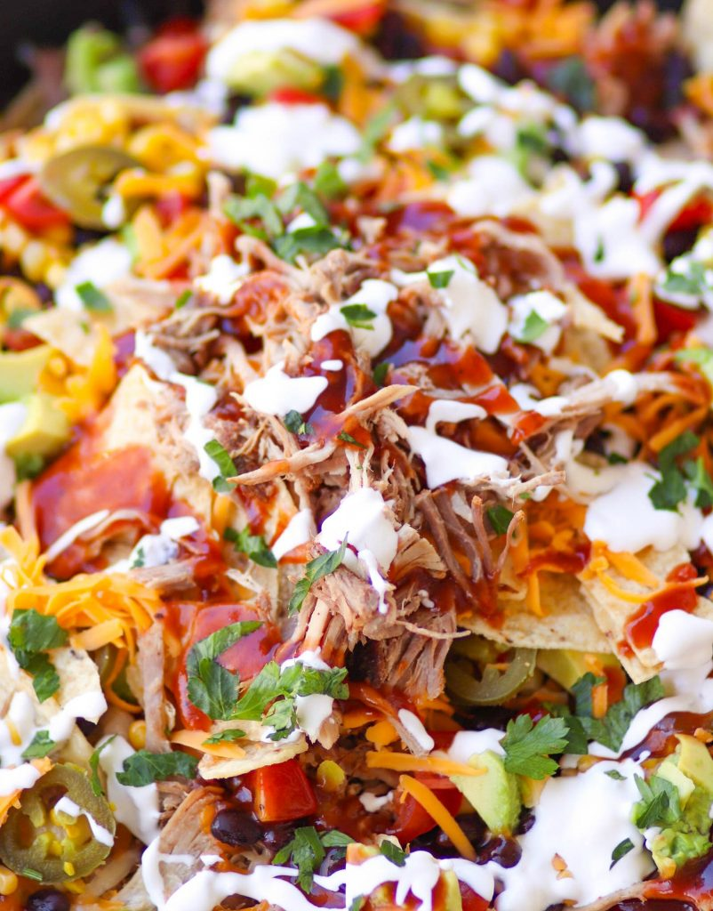Pulled Pork cooked in the Instant Pot is tender and juice. It's then turned into nachos loaded with cheese, beans, corn, peppers, avocado, BBQ sauce and sour cream for a dish that is out of this world!