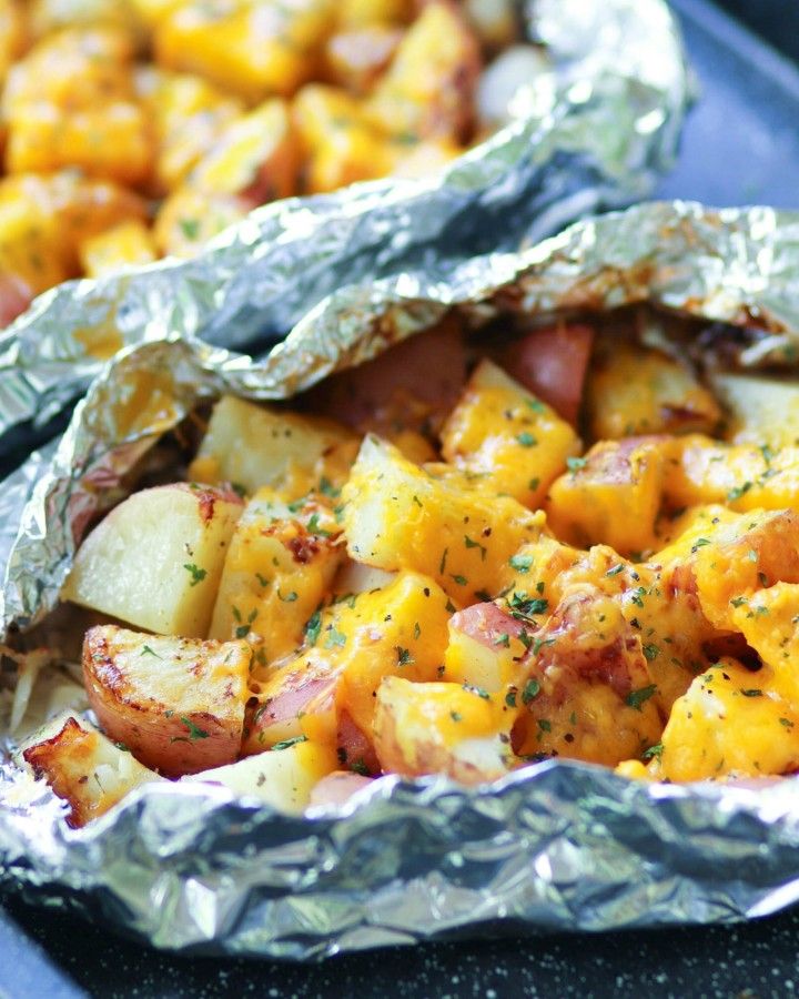 Red potatoes flavored with ranch seasoning then cooked on the grill in foil packets are loaded with cheese for a side dish that is perfect for any cookout or BBQ!
