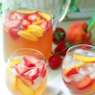 Rose sangria flavored with peach schnapps, peach juice with fresh fruit is a cool drink that's excellent for summertime!,
