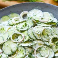 Creamy Cucumber Salad is a simple side dish that's full of fresh flavor. Make with cucumbers and onions in a dressing of sour cream, vinegar, sugar, dill, salt, pepper and garlic it's a cool creamy salad to enjoy any time of the year!