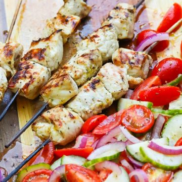 Grilled Chicken Souvlaki Skewers are juicy and tender. Make with lemon juice, oregano, garlic, salt and pepper. Add in a chopped salad with tomatoes, onions and cucumbers and you've got a meal your friends and family will love!