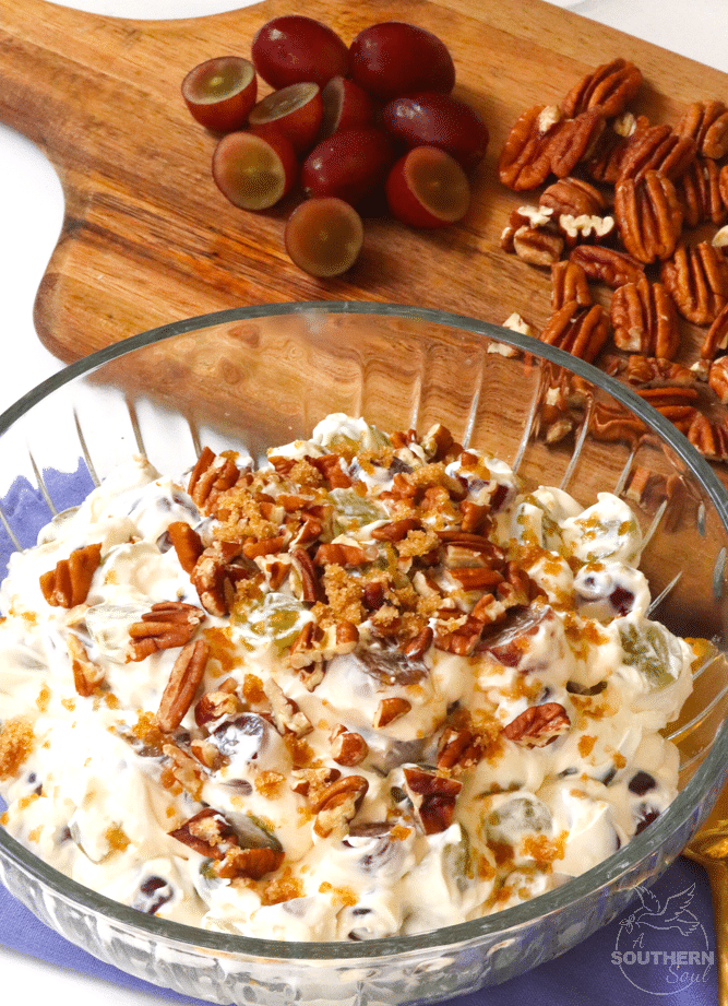 Simple grape salad made with red and green grapes, cream cheese, sour cream and sugar then topped with pecans and brown sugar is an irresistible side dish or dessert!