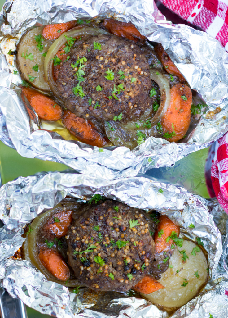 Hobo Dinner Foil Packs are made with ground beef, sliced potatoes, carrots and onions seasoned with butter and Montreal Steak Seasoning. They can be cooked on the grill, over a camp fire or in the oven.