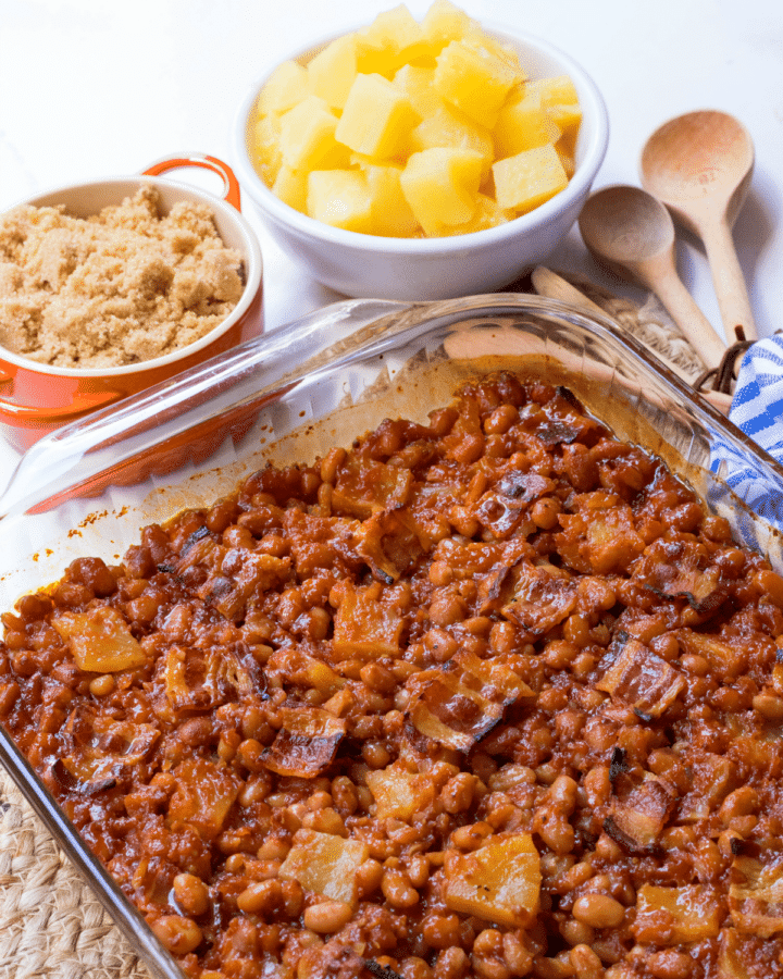 Pineapple BBQ Baked Beans made with canned beans, your favorite BBQ sauce, onion, brown sugar, whole grain mustard, pineapple chunks and bacon. They are baked to perfection and make a great side dish for any cookout, potluck, covered dish supper, and are great when you need to feed a crowd!