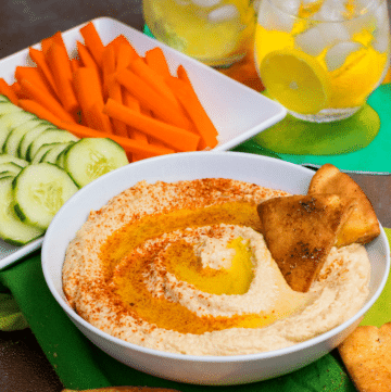 Roasted Garlic Hummus is so delicious and easy to make. Made with olive oil, roasted garlic cloves, chickpeas, lemon juice, tahini, salt and red pepper flakes that are blended together until silky smooth.