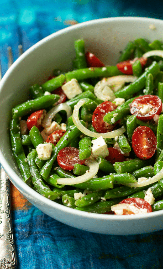 Green Bean Salad made with fresh bean, tomatoes, onions and feta cheese, tossed into a light lemony dressing is the perfect side dish for any meal!