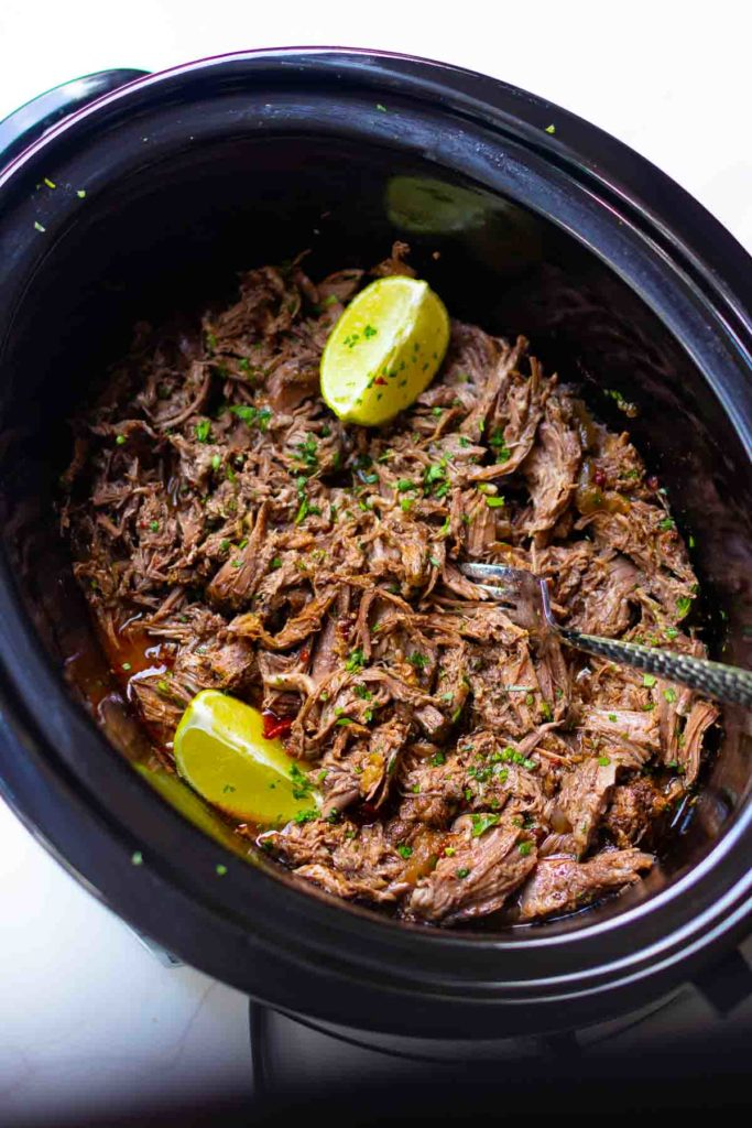 Slow Cooker Mexican Shredded Beef is easy to make and perfect for tacos, nachos, burritos or served with rice and beans. Make with chuck roast, chipolte peppers, onions, lime juice, beef stock, taco seasoning and garlic.
