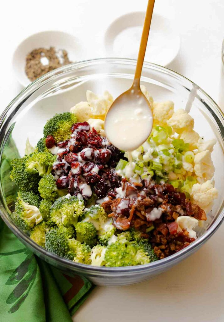 Broccoli Cauliflower Salad with creamy dressing on spoon.