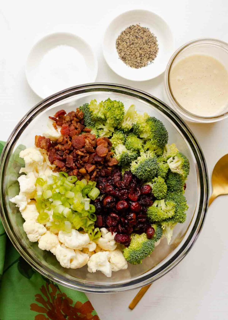 Broccoli Cauliflower Salad ingredients with spoon.