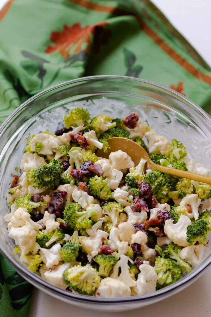 Broccoli Cauliflower Salad in mixing bowl with spoon.