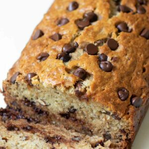 Chocolate Chip Banana Bread with golden brown top sliced for serving.
