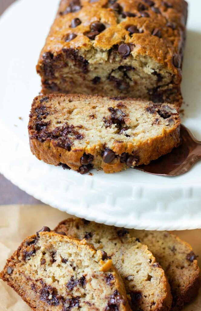 Chocolate Chip Banana Bread with pecans sliced on cake stand.