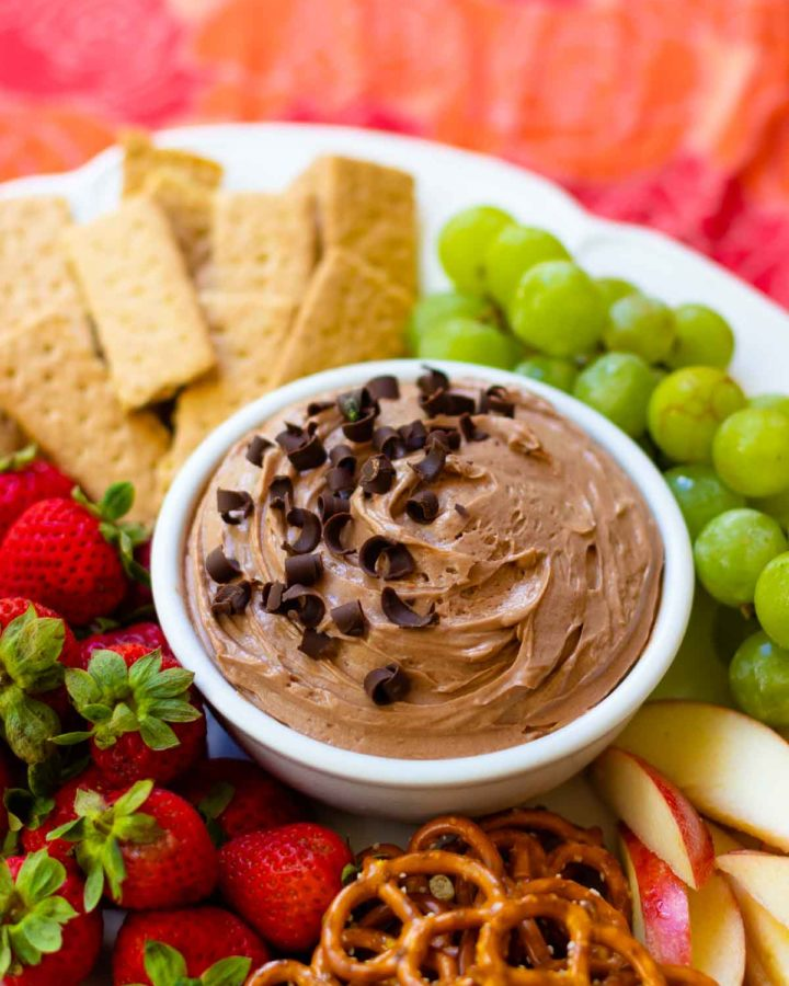 Chocolate Dip in bowl on fruit platter with cookies and pretzels.