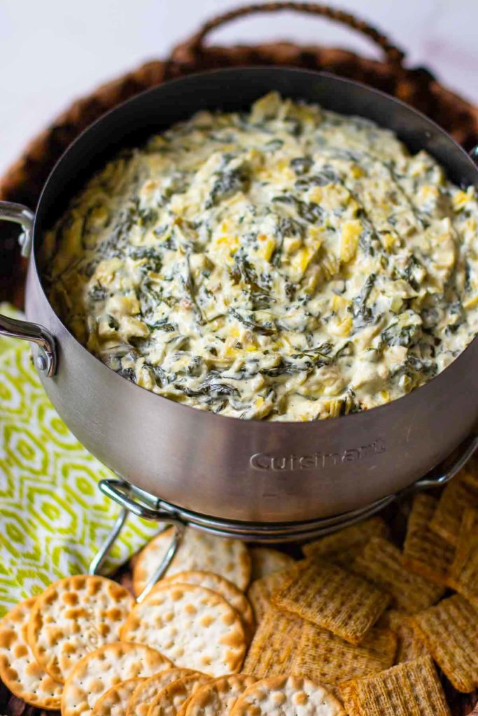 Spinach Artichoke Dip in small crock pot with crackers.
