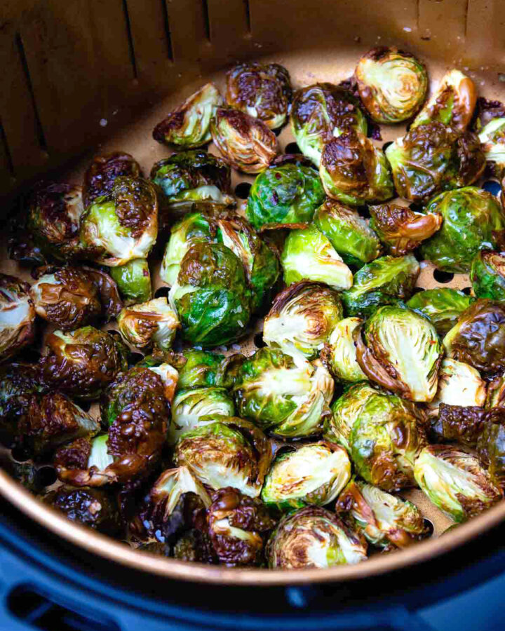 Perfectly cooked brussel sprouts in the basket of an air fryer.
