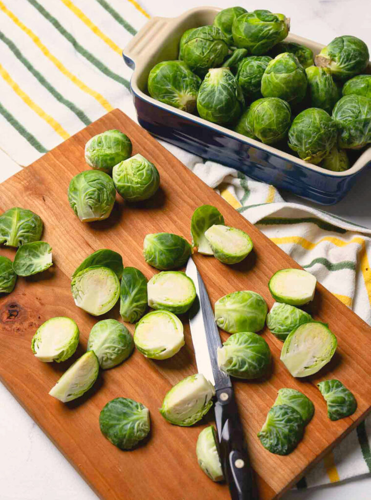 Raw brussel sproutson a cutting board with a knife to be cooked in an air fryer.