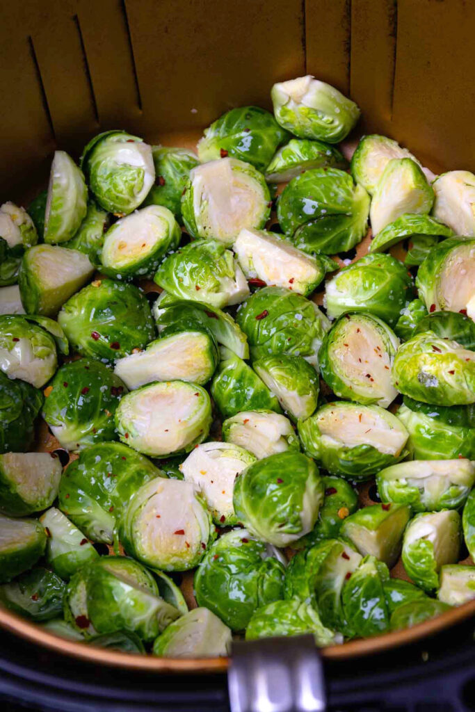 Raw brussel sprouts with olive oil, salt and pepper in basket of the air fryer.