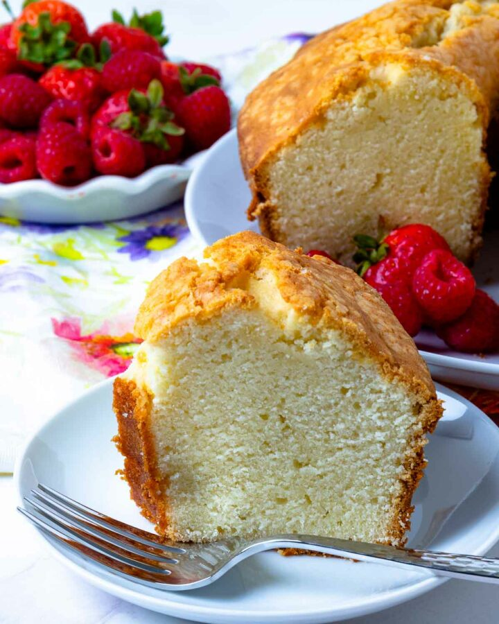Slice of Southern Pound Cake with berries on a plate with fork ready to be enjoyed.
