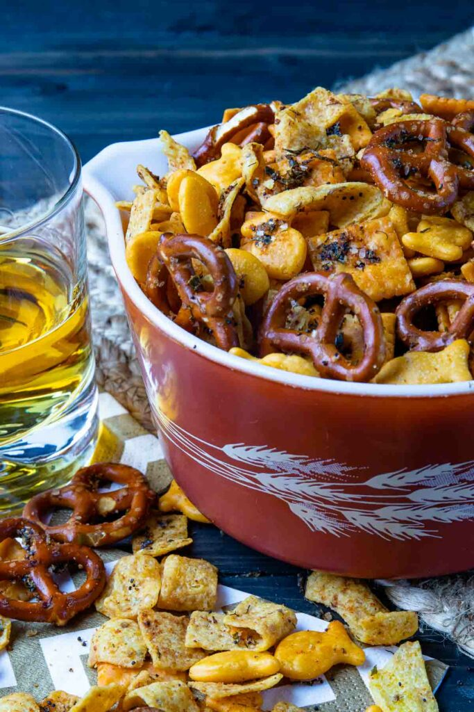 Spicy Cheese Cracker Snack Mix in a bowl with a drink for appetizers.