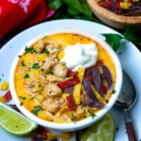 Easy to make White Chicken Chili in a bowl topped with cool sour cream and tortilla chips is totally delcious!