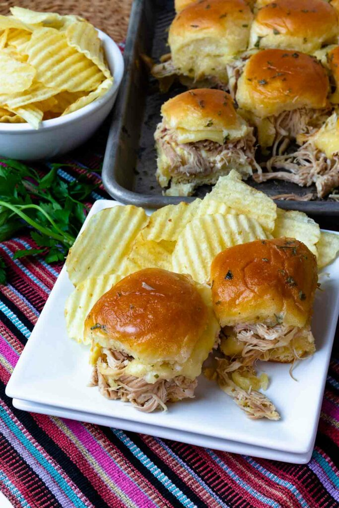 Sliders made with Crock Pot Mississippi Chicken and cheese served with potato chips.