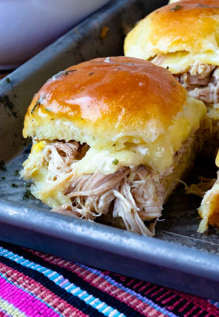 Toasted bun loaded with Crock Pot Mississippi Chicken and cheese.