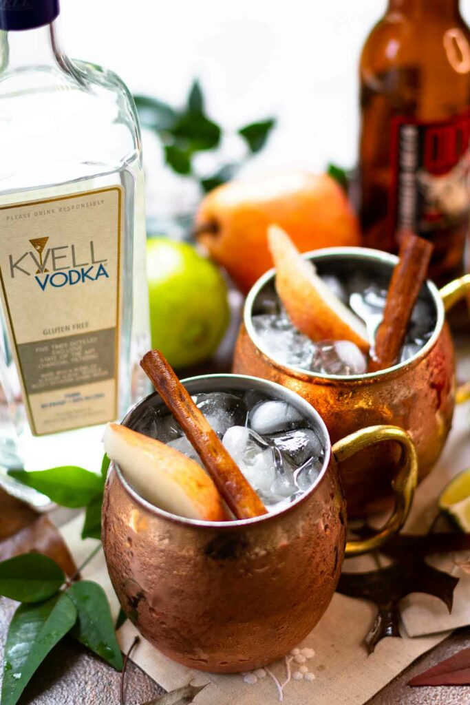 Kvell vodka and copper mugs filled with moscow mules.