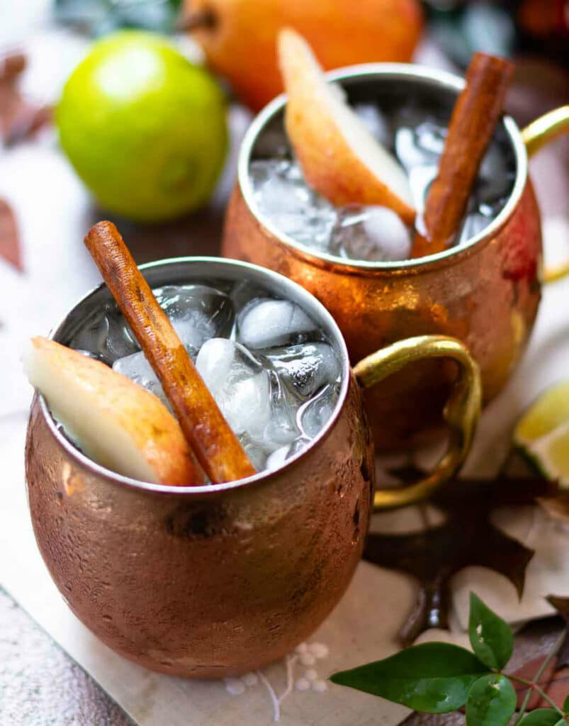 Ice, sliced pears and cinnamon sticks in copper mugs filled with Spiced Pear Moscow Mule drink.