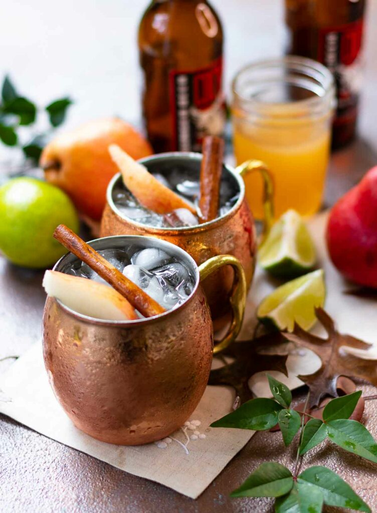 Two Moscow Mule copper mugs filled with spiced pear drink.