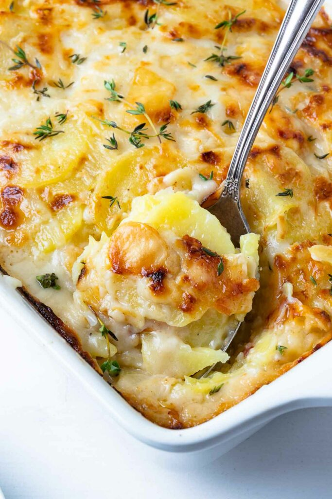 Scalloped Potatoes scooped with a spoon are beautifully cooked and delicious.