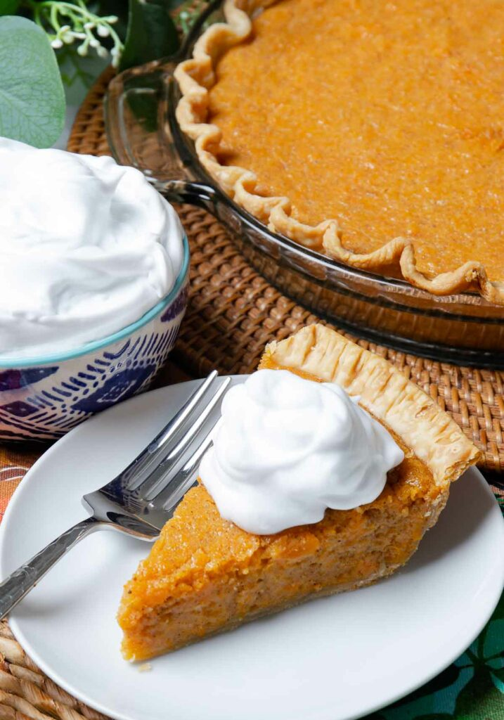 Classic Sweet Potato Pie with whipped cream for dessert at Thanksgiving.