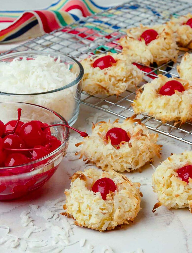 Ambrosia Cookies with red cherries and white coconut on a rack cooking.