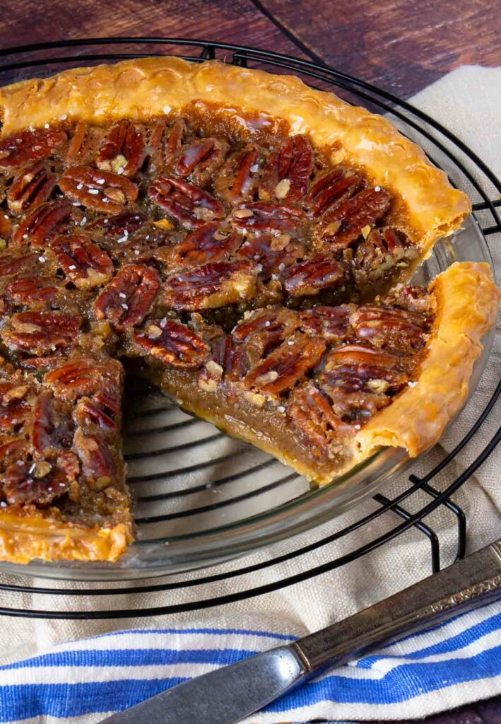 Maple Bourbon Pecan Pie sliced in pie pan on cooling rack.