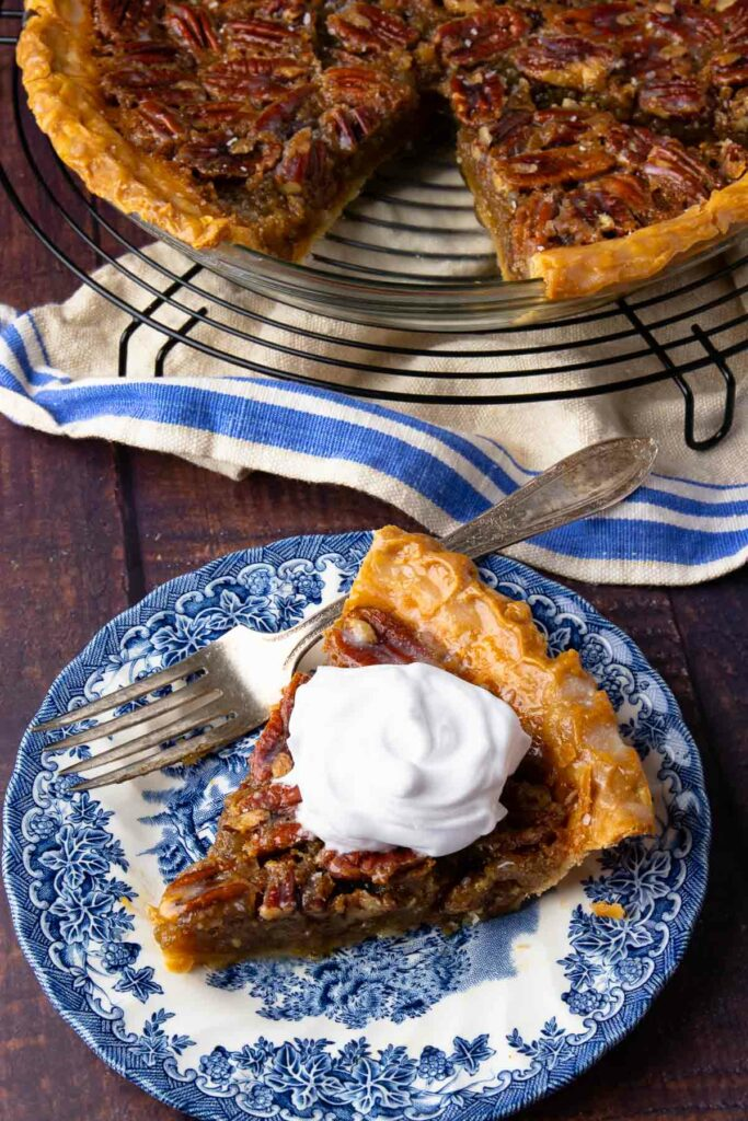 Maple Bourbon Pecan Pie slice with whipped cream on a blue plate with fork.
