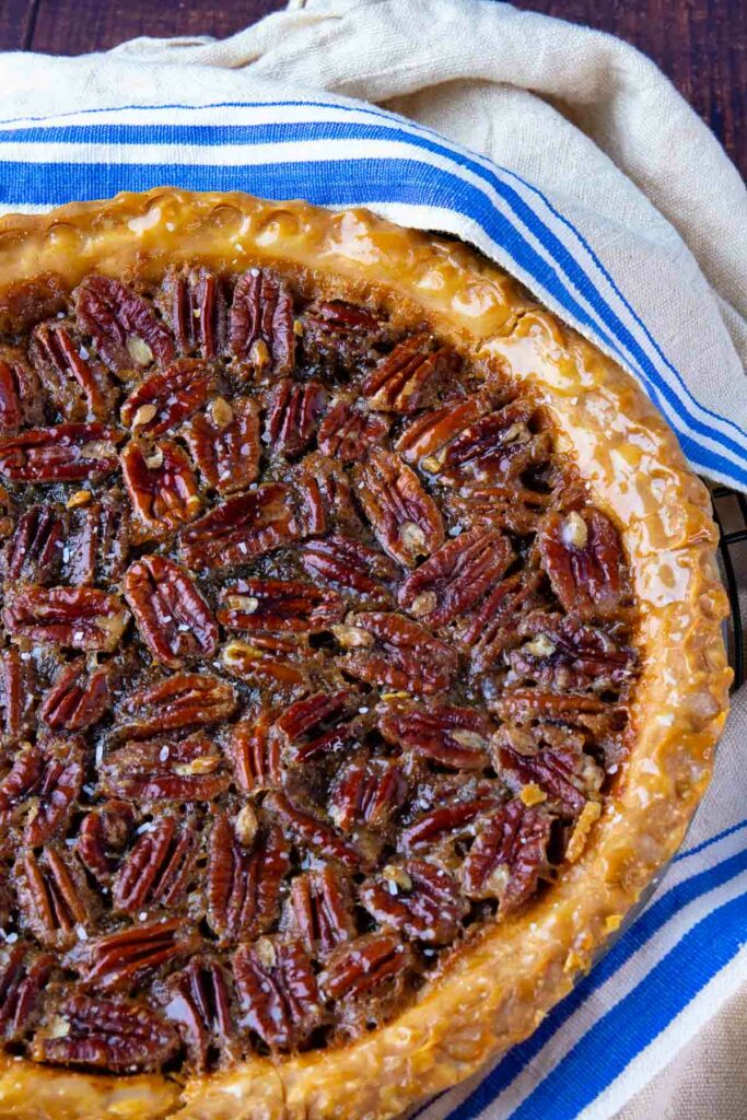Maple Bourbon Pecan Pie with buttery crust cooling on a tea towel.