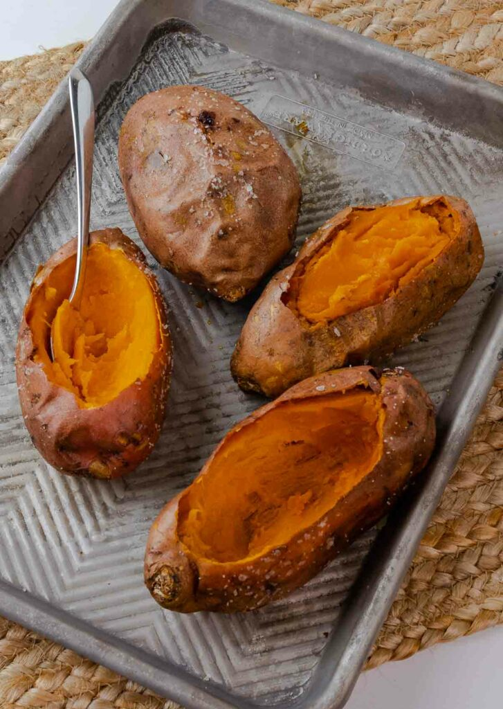 Twice baked sweet potatoes hollowed out for baking on a sheet tray.