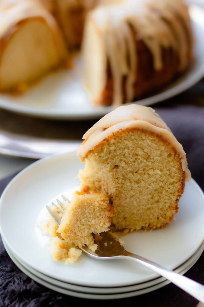 Buttermilk Pound Cake with brown butter icing sliced on a plate with a fork.